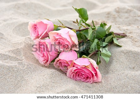 pink rose bouquet in beach sand