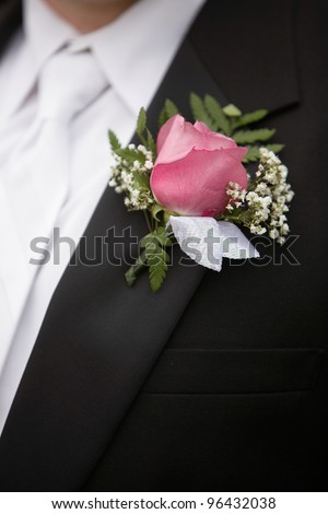 Pink rose boutonniere flower on groom's wedding coat - stock photo