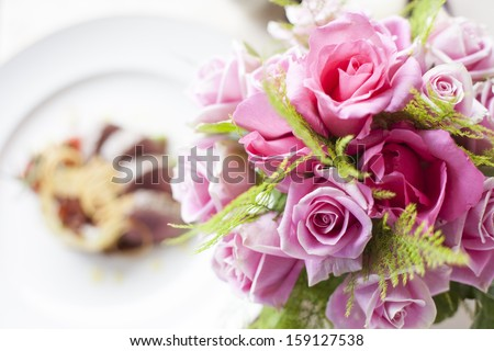 Pink rose flower on front of Beef medallions - stock photo
