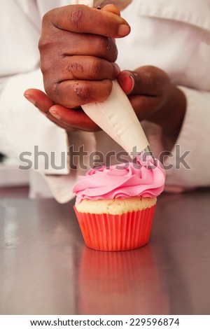 Pink rose icing being piped onto a cupcake - stock photo