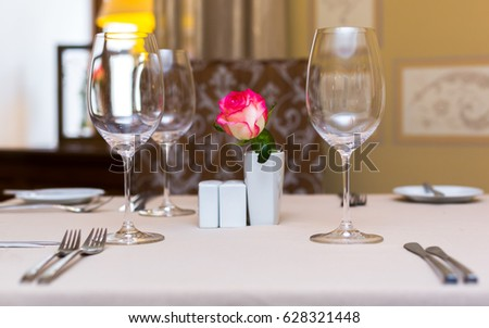 Pink rose in a vase as table decoration. Table setting