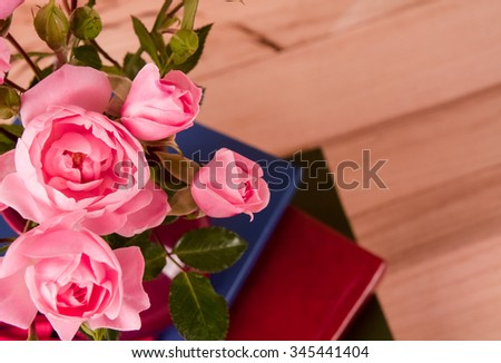 Pink rose on wooden table background with retro glasses and white hand made paper as a copy space, Romantic floral theme