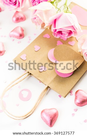 Pink roses and hand crafted gift bag on a white background.
