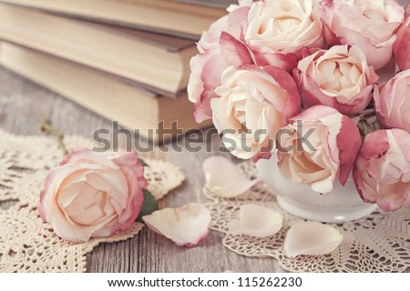 Pink roses and old books on wooden desk - stock photo