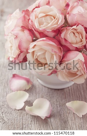 Pink roses and petals on wooden desk - stock photo