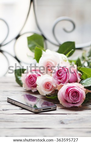 Pink roses and smartphone on the wooden table, selective focus