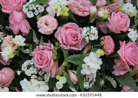 Pink roses and white flowers in a wedding arrangement