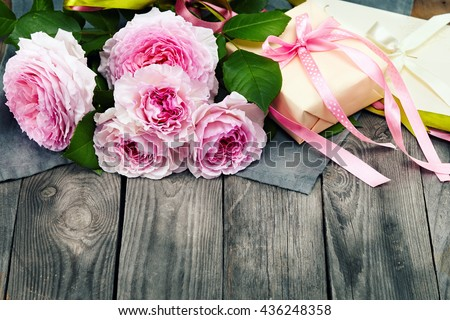 pink roses bouquet and gift box on a wooden background - stock photo