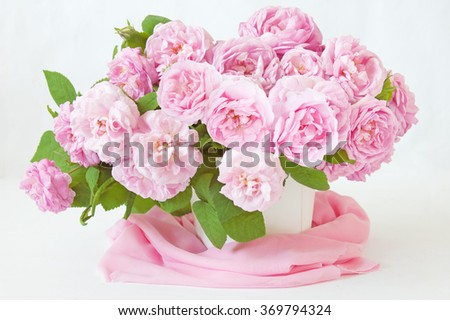 Pink roses bunch in vase on artistic background. Still life with pink roses bunch - stock photo