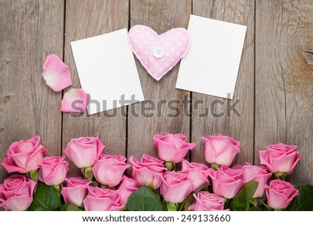 Pink roses, handmaded toy heart and valentines day blank greeting cards or photo frames over wooden table. Top view with copy space - stock photo