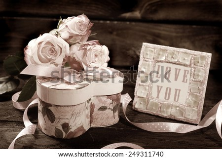 pink roses , heart shaped gift box and frame on wooden background in sepia  - stock photo
