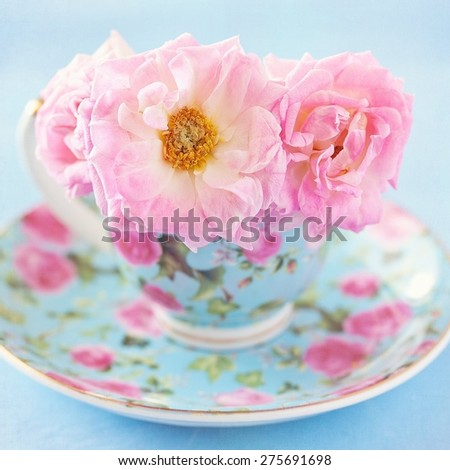 Pink roses in a beautiful blue porcelain cup on a table. - stock photo