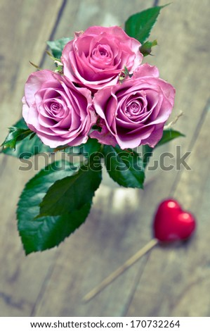 Pink roses in a glass bottle - stock photo