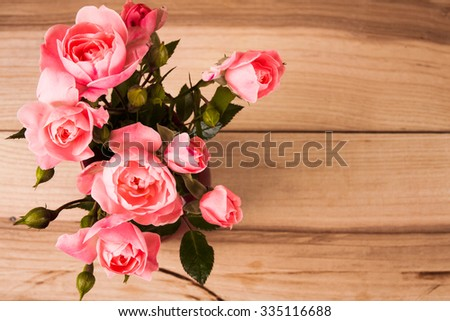 Pink roses in a vase on wooden background - stock photo