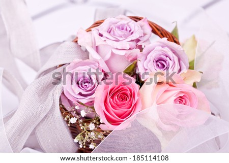 pink roses in brown basket with withe bow