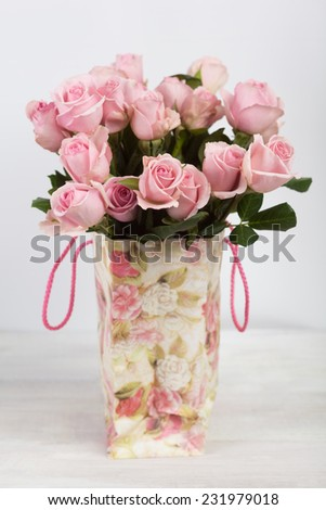 Pink roses in shopping bag with floral ornaments - stock photo