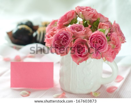 Pink roses in white cup for celebration, selective focus