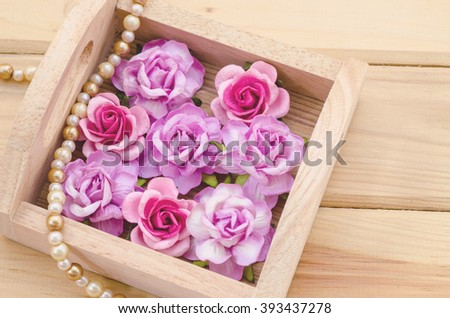Pink roses in wooden box on desk. - stock photo