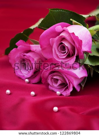 Pink Roses on a romantic red satin background - stock photo