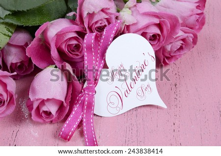 Pink Roses on pink wood background closeup with Happy Valentines Day heart shape gift tag. - stock photo