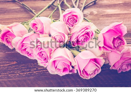 Pink roses on wood table.