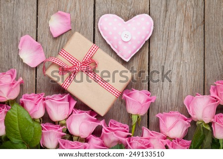 Pink roses over wooden table with valentines day gift box and handmaded heart toy - stock photo