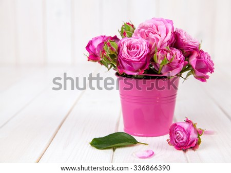 Pink roses(peony) in vase on white wooden background. flowers - stock photo