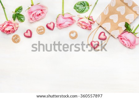 Pink roses with chocolate heart, shopping bag and round sign with message for you and with love on light background, top view.  Valentine Day or Birthday greeting card. Border.
