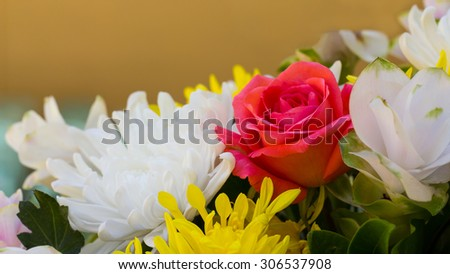 Pink roses with white flowers and yellow decorations together beautifully, but wither. - stock photo