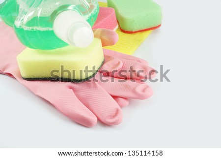 Pink rubber gloves, colorful sponges and detergent