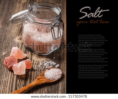 Pink salt in wooden spoon and in glass jar  - stock photo