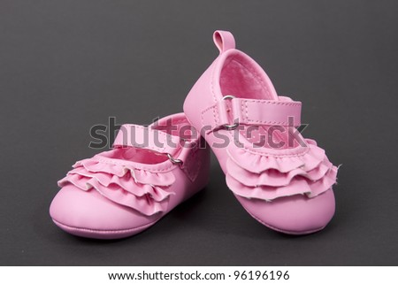 Pink satin baby shoes - stock photo