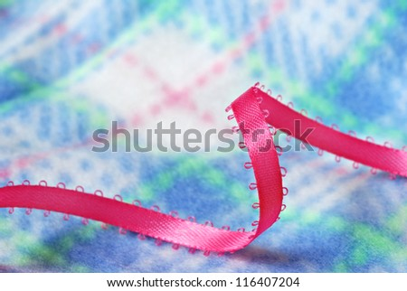 Pink satin ribbon on soft fleece baby blanket with pastel plaid design.  Macro with shallow dof. - stock photo