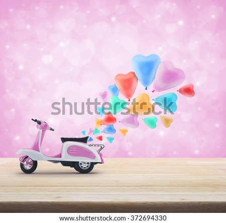 Pink scooter toy with colorful heart love balloon on wooden table over light pink heart bokeh background, valentine concept