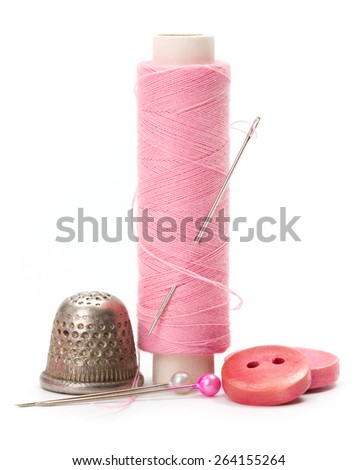 Pink sewing accessories: thread, needle, buttons and thimble - stock photo