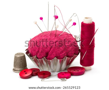 Pink sewing accessories: thread, needle, buttons, thimble and pincushion