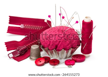 Pink sewing accessories: thread, needle, buttons, thimble, zipper and pincushion