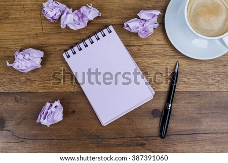 Pink sheets notebook with spiral in the center of the wooden dark brown table with black pen aside and cup of coffee on top right and crumpled paper balls from above - stock photo