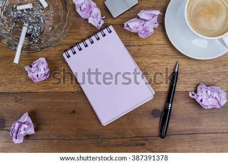 Pink sheets notebook with spiral on the wooden dark brown table with black pen aside and cup of coffee on top right and crystal glass ashtray with lighted cigarette crumpled paper balls from above - stock photo