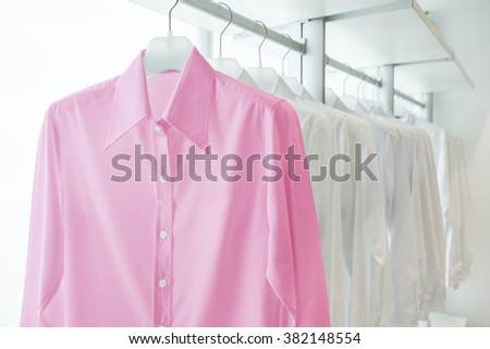 pink shirts hanging on white built-in cloths racks, with drawers and other accessories - stock photo