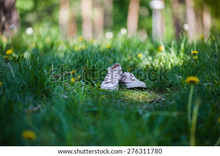 Pink shoes on the green meadow - stock photo