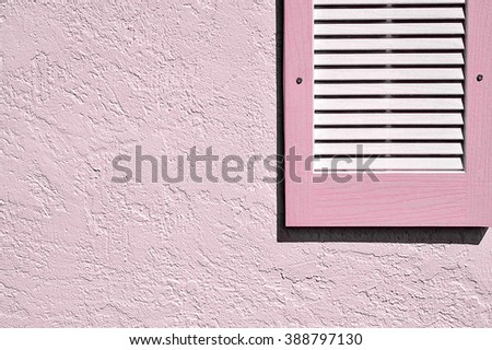 Pink shutter and exterior stucco wall - stock photo