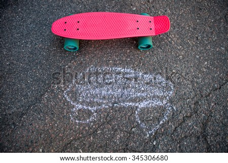 Pink skateboard on asphalt with a chalk drawing - stock photo