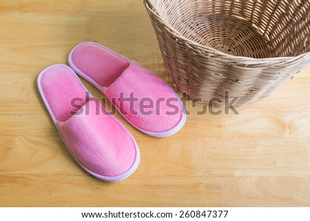 Pink slippers and basket on wooden background