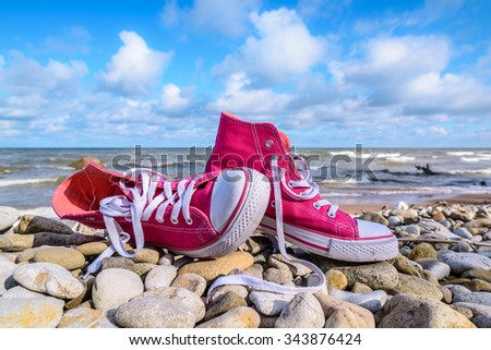 Pink sneakers on the seashore - stock photo