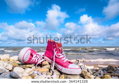 Pink sneakers on the stony beach - stock photo