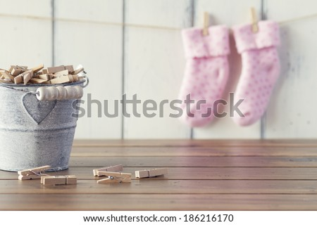 Pink socks for baby girl hanging on rope with clothespins. A metal bucket with clothespins. Vintage look. - stock photo