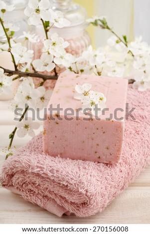 Pink spa set: bar of handmade natural soap and towel - stock photo