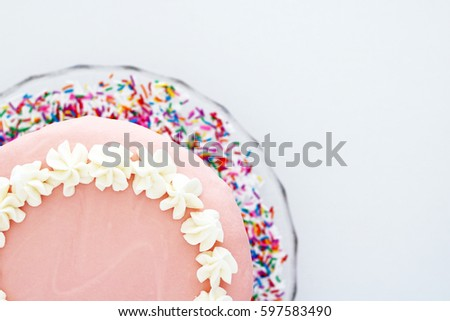 Pink Sprinkles Vanilla Birthday Cake on Vintage Glass Platter with White Background Above Angle