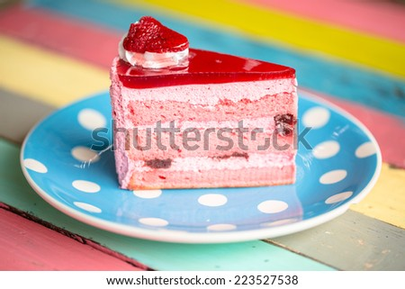Pink strawberry cake on white blue design plate on multicolor wood desk - stock photo